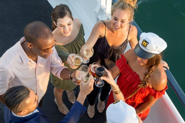 Group of friends cheering drinks on a boat