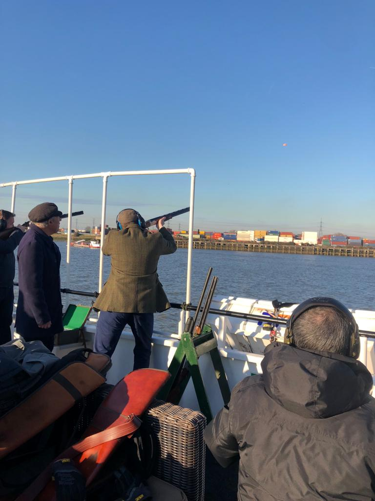 Man on boat shooting clay pigeons