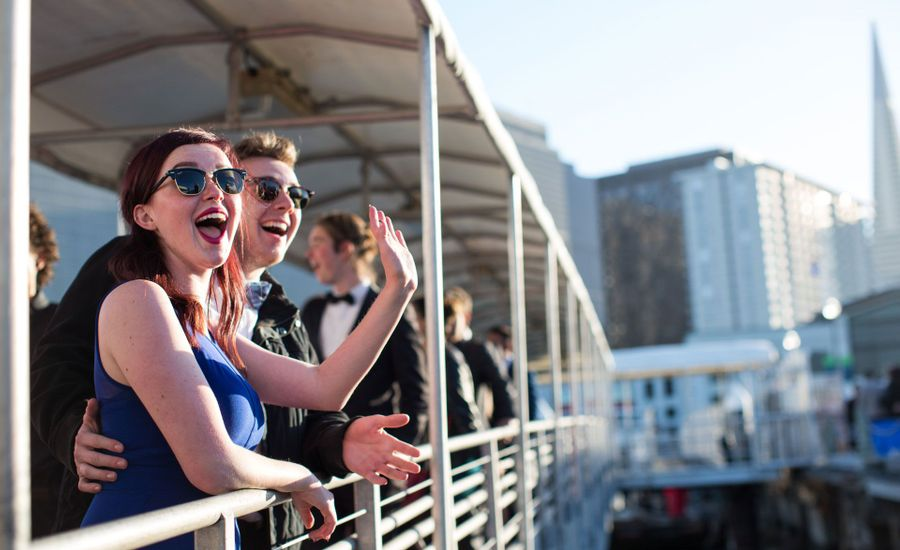 Couple waving from railing of boat.