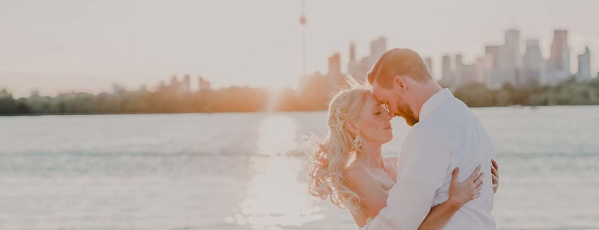 Newlyweds foreheads together water and Toronto in background