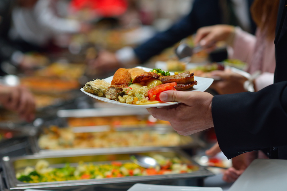 Hand holding plate of food in buffet line.
