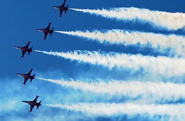 5 jets in formation leaving contrails behind them.