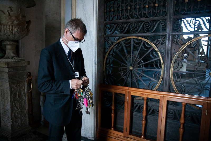 A man wearing a face mask holding a large key chain with many keys attached.